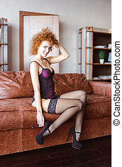 Alluring woman sitting on sofa in lace corset and stockings