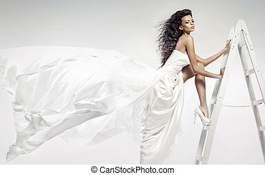 Alluring young tawny woman wearing white dress