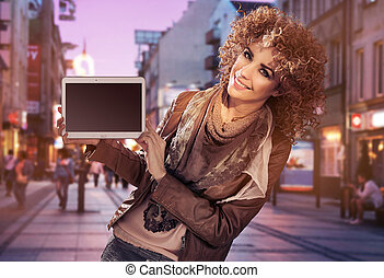 Alluring young woman holding a tablet