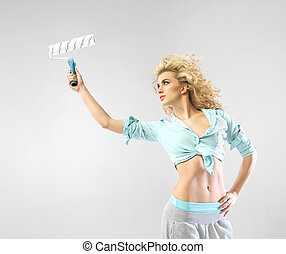 Alluring young woman holding the paint roller