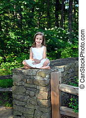 Young girl sits on a stone fence in a white eyelet dress. She is surrounded by the wild beauty of the Birmingham Botanical Garden in Birmingham, Alabama.