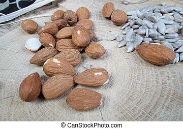 Almond and sunflower healthy seeds on wooden board with pattern