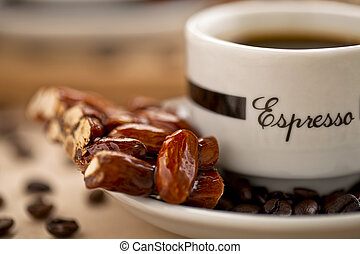 A close-up image of almond confection and a dark coffee on a white saucer with beans