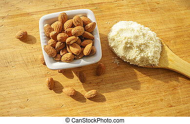 Almond flour in a wooden spoon on a background of nuts almonds.