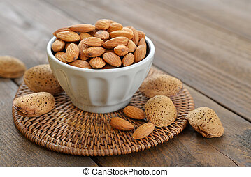 Almond in bowl on wooden background closeup