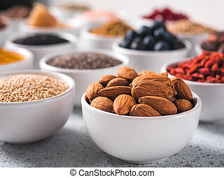 Almond in small white bowl and other superfoods