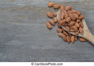 almond in wooden spoon on wood background