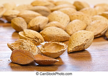 Almond kernel with shells on wooden background