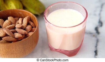 almond nut , banana and milk on table .