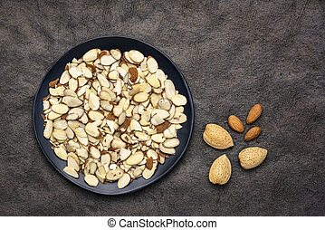almond slices and nuts on a black plate