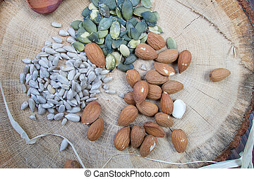 Almond, sunflower and pumpkin healthy seeds on wooden board with pattern