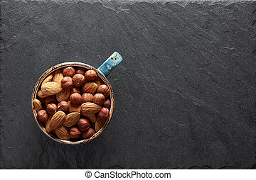 almonds and hazelnuts in a cup on stone table. Top view