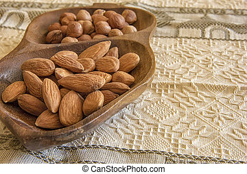 Almonds and hazelnuts in the wooden bowl on the table, close-up