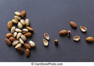 Almonds and pistachios on black background, healthy food concept