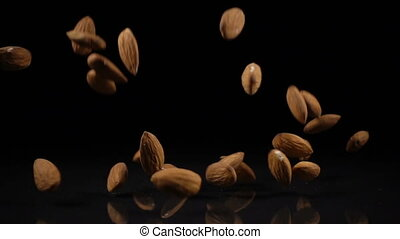 almonds fall onto a hard black surface, slow motion