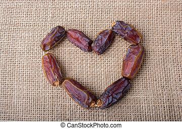Almonds form a heart shape on canvas