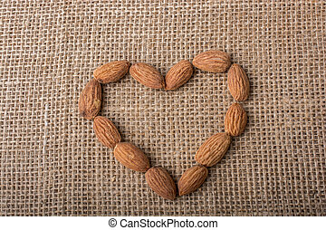Almonds form a heart shape on canvas