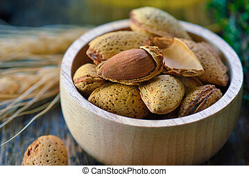 Almonds in a bowl on wooden background