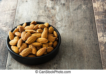 Almonds in black bowl on wooden table