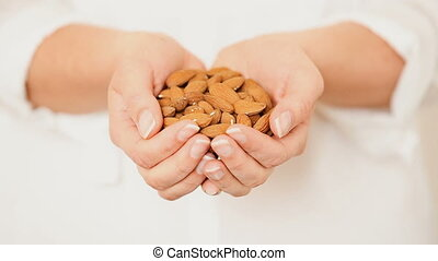 Almonds in Cupped Hands - Caucasian female model pouring...