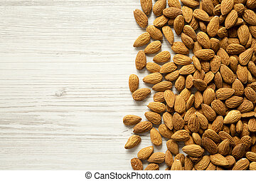Almonds on a white wooden background, top view. Copy space.
