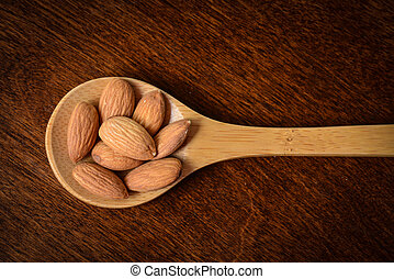 Almonds on a Wooden Spoon with Wood Texture Background