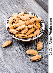 Almonds on rustic wooden background.