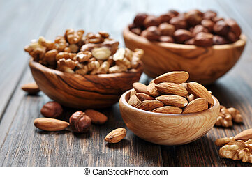 Almonds, walnuts and hazelnuts in wooden bowls on wooden ...