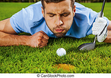Almost in. Close-up of young golfer blowing at the ball...