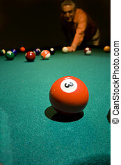 Almost there - A man at the pool table � aiming. Dark...