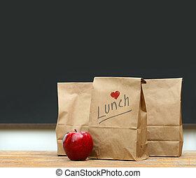almuerzo, bolsas, con, manzana, en, escritorio de la escuela