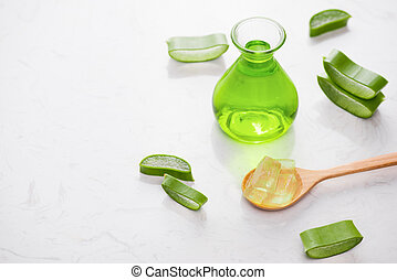 Aloe vera essential oil and aloe leaves on a white background.