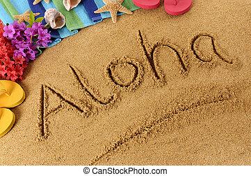 The word Aloha written on a sandy beach, with flowers, beach towel, starfish and flip flops.