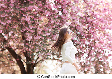 Alone beautiful girl with a romantic hairstyle and a professional make-up enjoys a smell of pink colors in a garden. The girl dreams. A portrait of the beautiful girl model in the spring in the park.