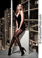 Alone beautiful woman sitting on window and looking on night city