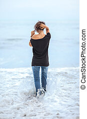 Alone beautiful woman standing in the sea during storm