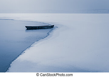 Alone boat on frozen lake in winter
