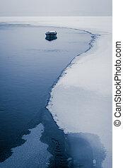 Alone boat on frozen river in winter