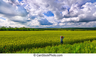 Alone girl viewing in wheat field with clouds stormy skies -...