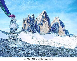 Alone hiker man bellow Tre Cime mountain massive building pyramid from pebbles.