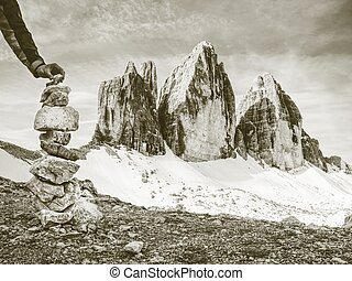 Alone hiker man building pyramid from pebbles.  Tre Cime di Lavaredo range,