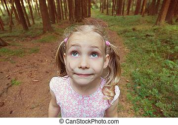 Alone little girl is afraid in dark forest. Closeup