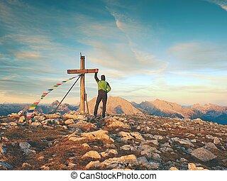 Alone man climber near the summit cross on peak, Dolomite Alps, Austria. Sunny windy evening.