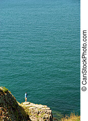 Alone man spectacular cliff in coast in Brittany, France