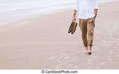 Alone man walking on the beach carrying leather shoes