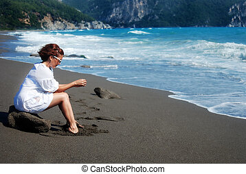Alone on the beach - Woman sitting alone on the rock at the ...