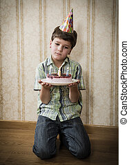 Alone sad boy with birthday cake on the floor