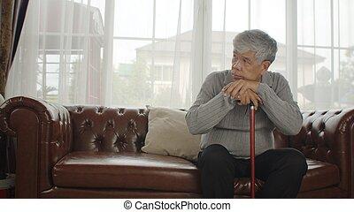 Alone senior man sitting on sofa with walking stick