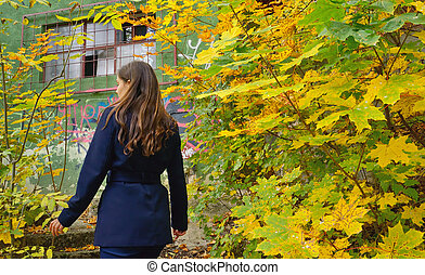 Teen girl in the autumn forest and hut