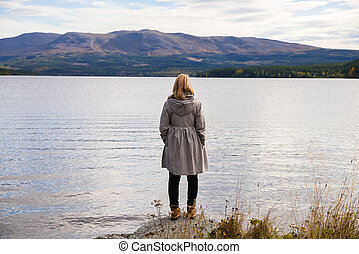 alone thinking woman standing on a stone